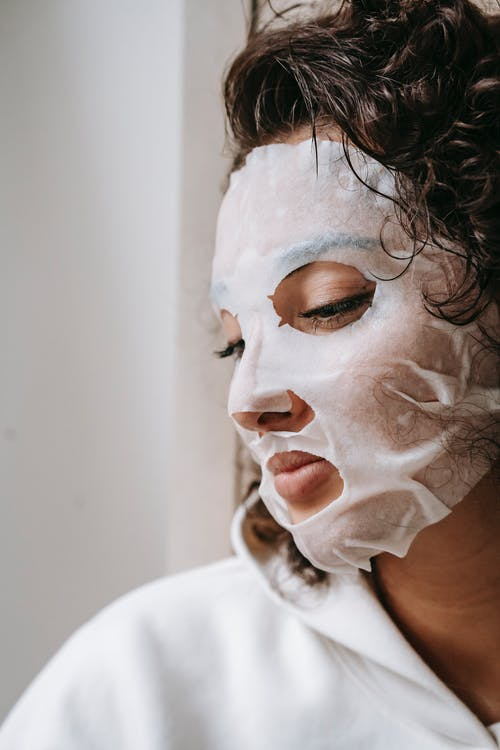 Side view of crop concentrated female with dark hair in facial mask looking down during daily skincare routine at home