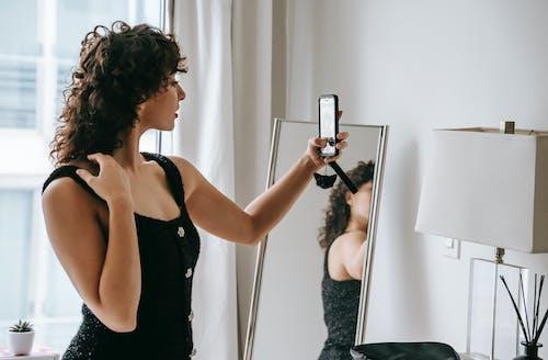 Beautiful woman taking selfie against mirror