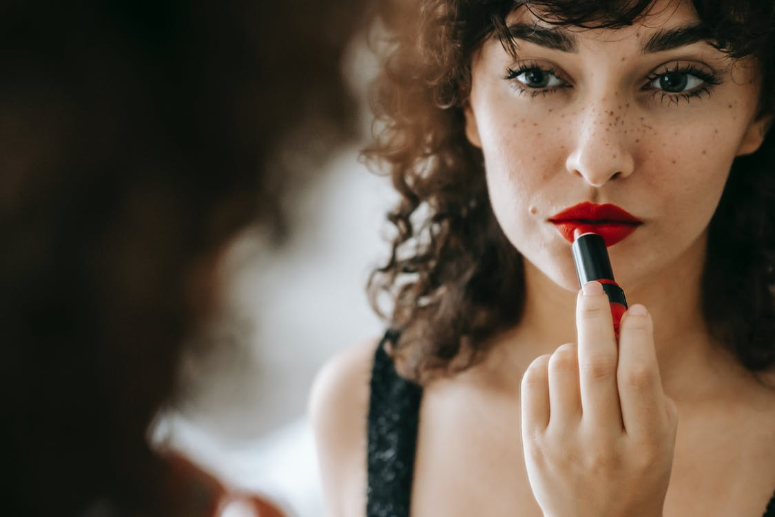 Attractive female with freckles and dark curly hair looking at mirror while applying red lipstick during cosmetic routine in room