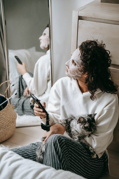 Calm woman in facial mask with cat surfing cellphone