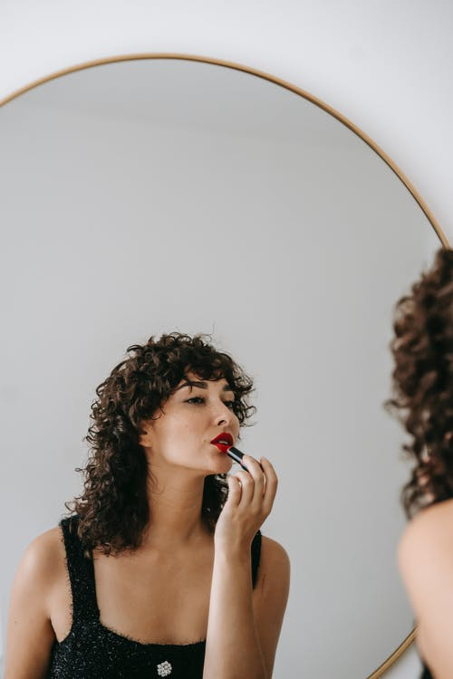 Charming female with dark curly hair wearing black outfit rouging lips while looking at mirror in room during beauty routine
