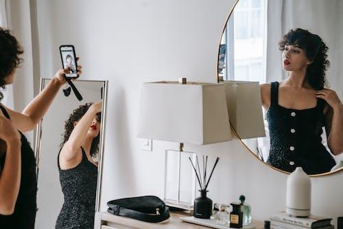 Charming woman taking selfie in room