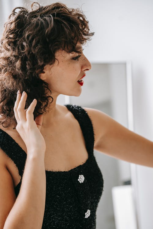 Side view of attractive female with curly hair and red lips wearing black clothes touching hair while standing in room against blurred background