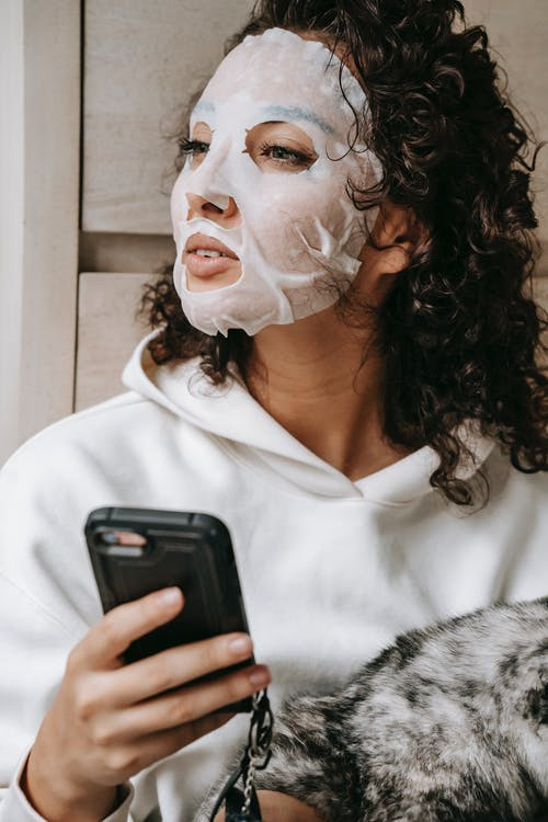 Dreamy woman in facial mask browsing smartphone