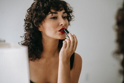 Crop gentle woman making up lips in front of mirror