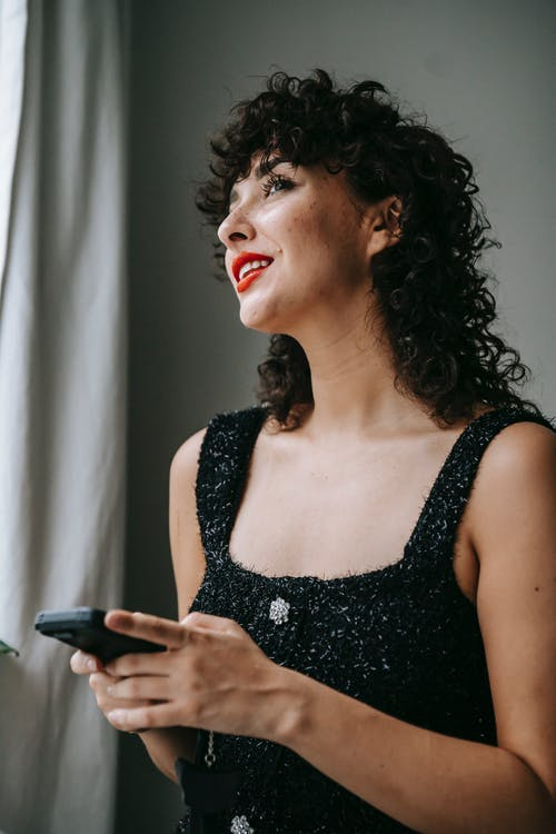 Smiling woman with smartphone at home in daytime