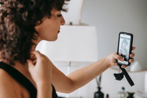 Crop elegant woman taking selfie on smartphone at home