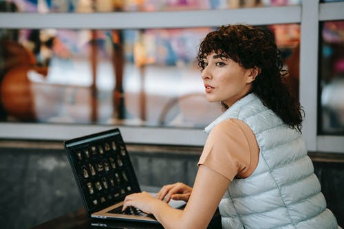 Dreamy female freelancer typing on laptop at cafeteria table