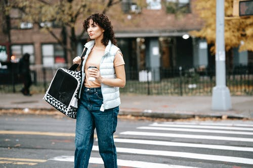 Woman with pet carrier and coffee to go crossing road