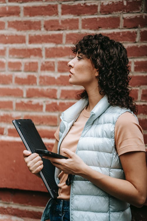 Attentive female remote worker with laptop and smartphone on street