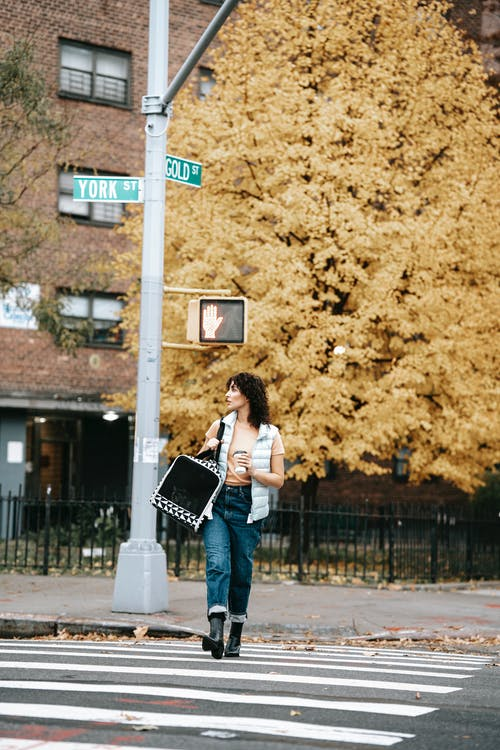Female in casual clothes with pet carrier and hot drink to go strolling on crosswalk in autumn city while looking away
