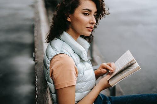 Young dreamy woman looking away while resting on bench with book in hands