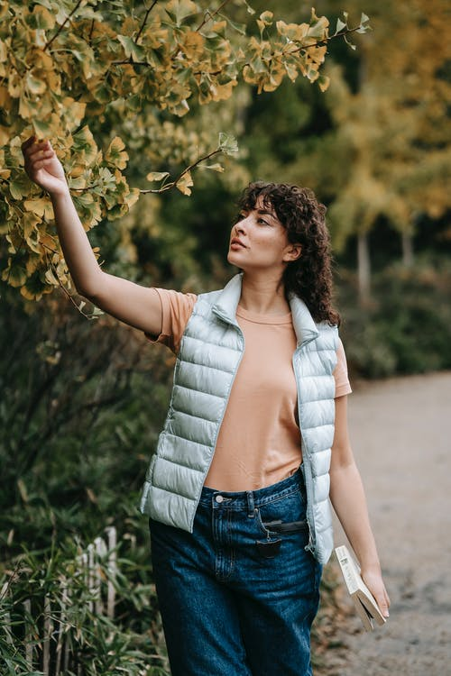 Pensive woman with curly hair in stylish clothes standing in park near green trees and touching leaves in daytime