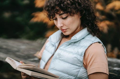 Crop pensive woman with brown curly hair in casual clothes sitting on street and reading book against autumn foliage in daytime