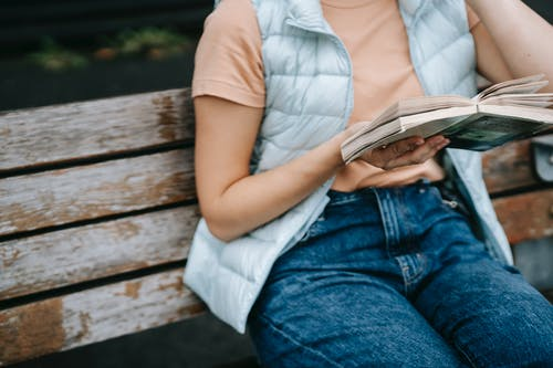 Woman reading book while sitting on wooden bench on street