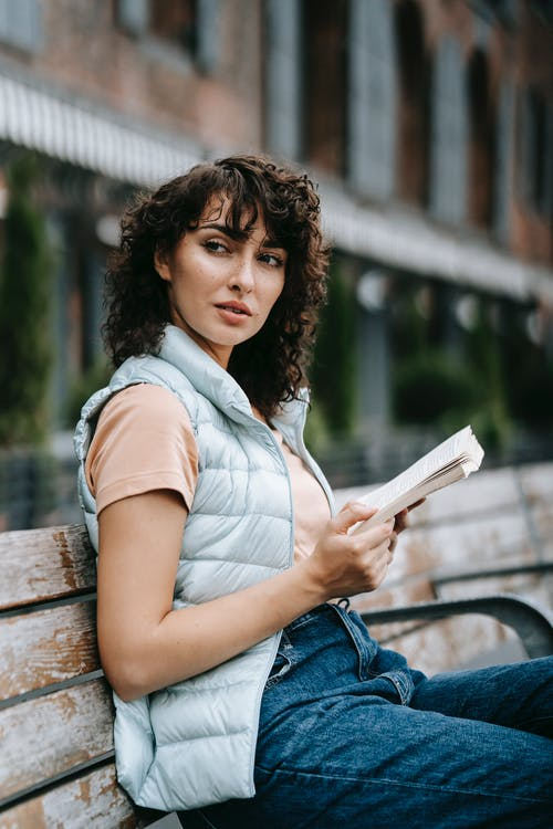 Charming woman with brown curly hair in casual clothes sitting on wooden bench and reading book on street in daytime