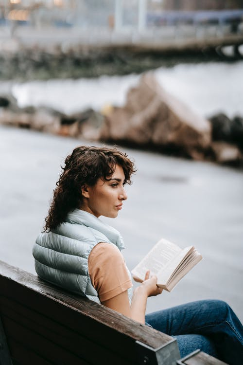 Calm female sitting on bench on street and reading book