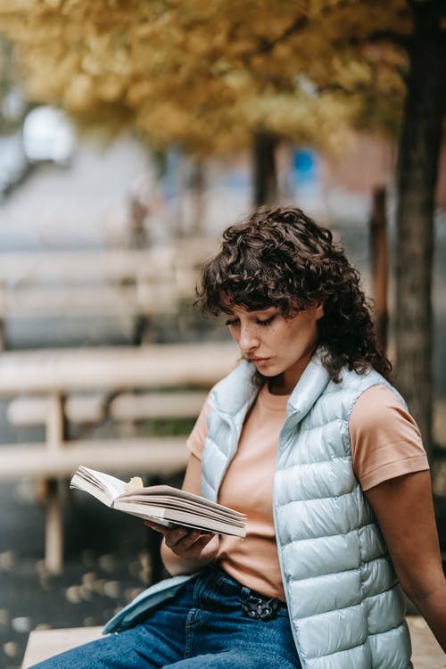 Concentrated woman with dark curly hair sitting on street and reading textbook against tree with autumn foliage in daytime