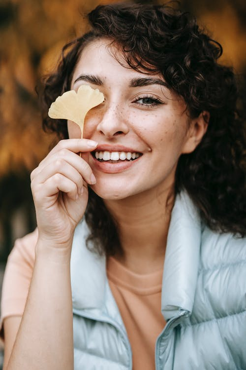 Happy woman with brown curly hair in casual clothes standing with yellow autumn leaf near face and looking at camera against blurred background