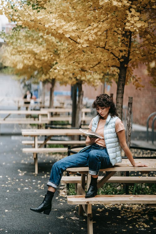 Pensive woman in trendy clothes sitting on wooden table and reading book on city street with autumn trees in daytime