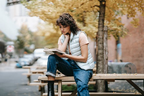 Pensive female in trendy outfit reading book while sitting on wooden table near autumn tree on city street in daytime