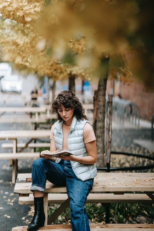 Pensive female sitting on street and reading book
