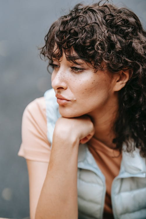Pensive curly haired female holding hand on chin while sitting and looking away