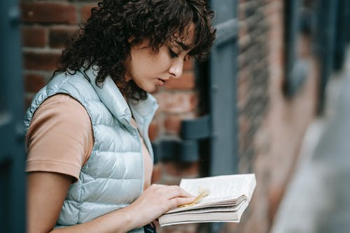 Side view of crop concentrated female standing near brick building and reading interesting story in book while spending time in city