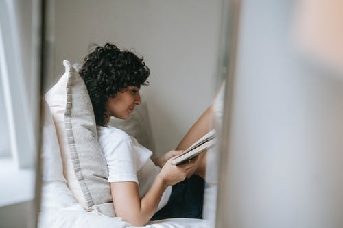 Side view of young curly haired female in sleepwear relaxing on soft bed with pillows while reading paper book