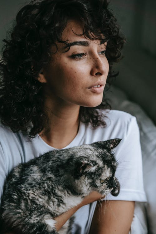 Crop dreamy young female with long curly hair and freckles sitting on bed with cat and looking away