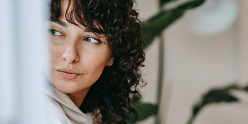 Charming female with freckles and dark curly hair sitting against green plants with leaves on blurred background in light room