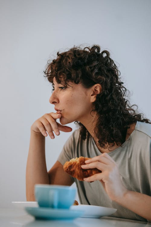 Pensive woman with croissant at table
