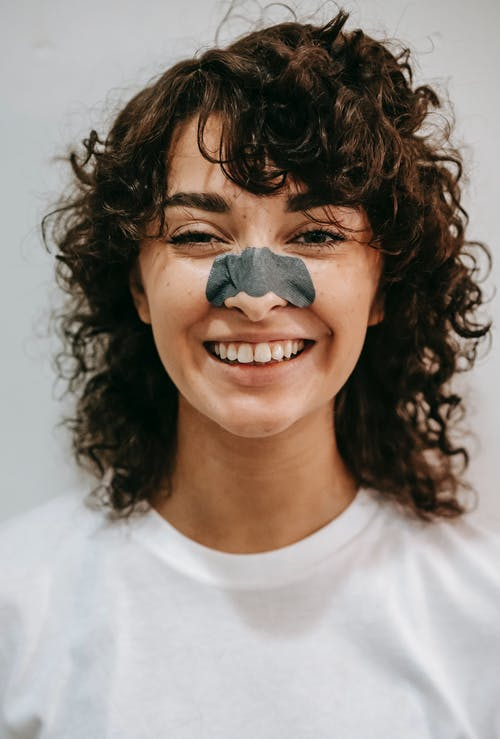 Cheerful female with curly hair and blackhead cleanse nose strip wearing white t shirt looking at camera on gray background