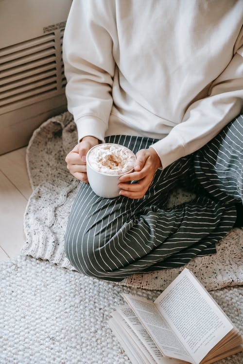 Crop woman with hot drink on floor