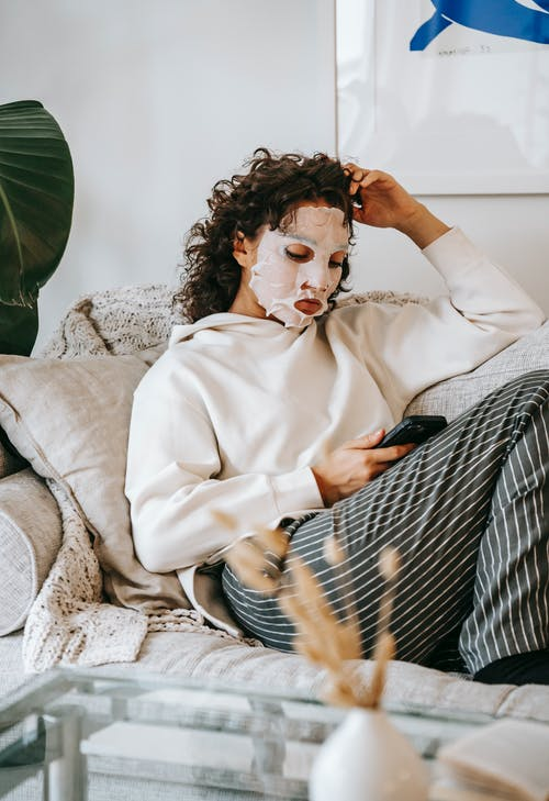 Woman with sheet mask surfing smartphone