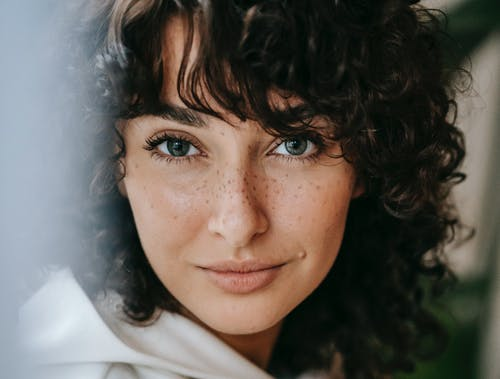 Headshot of attractive female with dark curly hair looking at camera against green leaves on blurred background in light room