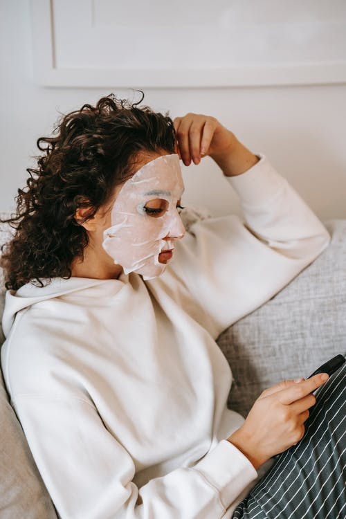 Side view of focused female with curly hair wearing sheet mask surfing cellphone while sitting couch with hand on forehead