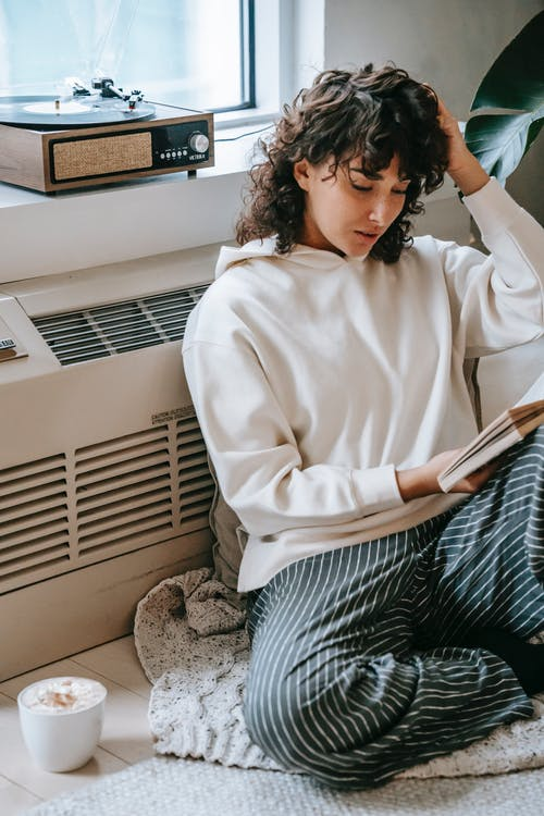 Thoughtful woman reading book in living room