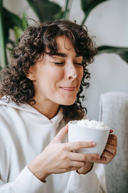 白いセラミックマグカップを保持している白いシャツの女性