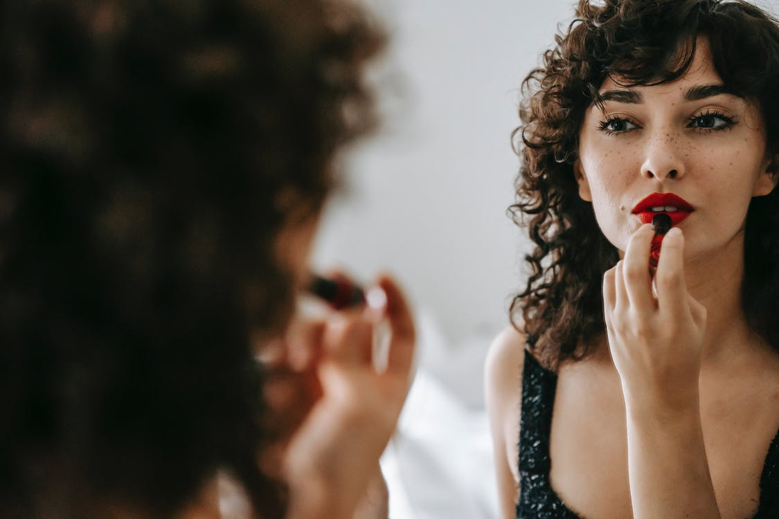 Beautiful female with curly hair applying red lipstick on lips while looking at mirror in light room against blurred background