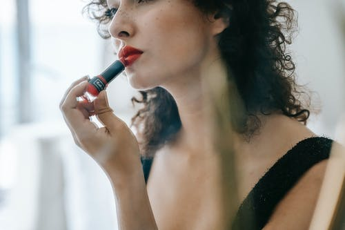 Content young woman applying red lipstick on lips