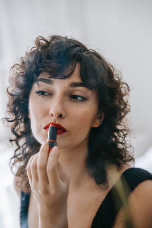 Content confident young female with makeup on face looking at mirror while spreading red lipstick on lips