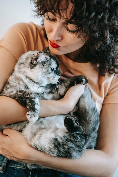 Mulher De Blusa Preta Segurando Um Gato Preto E Branco