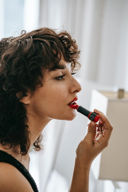 Young content woman applying red lipstick