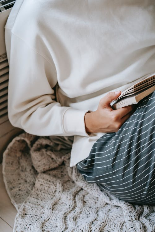 From above of crop anonymous female reading interesting story in novel while resting on knitted woolen plaid