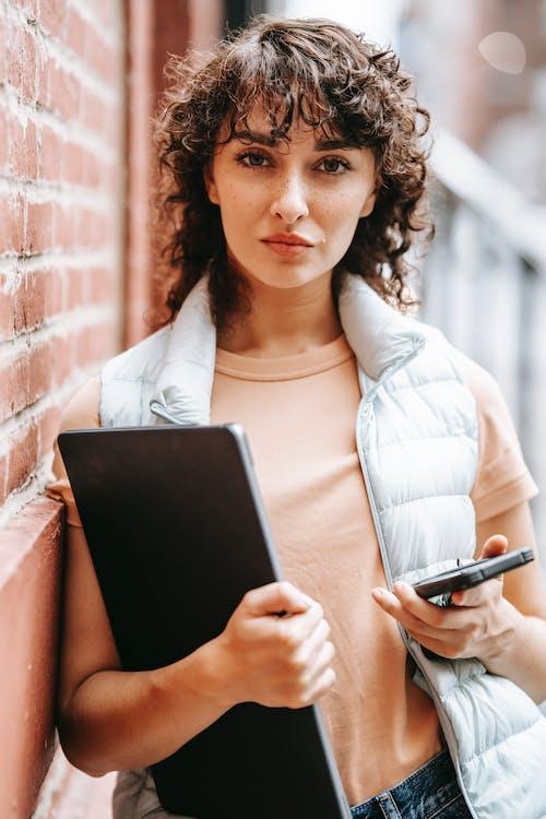 Mulher Com Camisa De Manga Comprida Branca Segurando Um Computador Tablet Preto