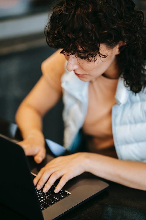 Mulher De Camisa Branca Com Botões Segurando Um Laptop Preto