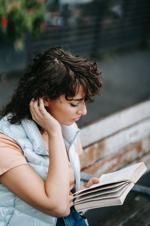 From above of young female with dark curly hair reading novel on street in daytime on blurred background