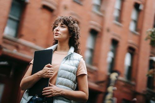 Mulher De Camisa Com Listras Brancas E Marrons Segurando Um Computador Tablet Preto