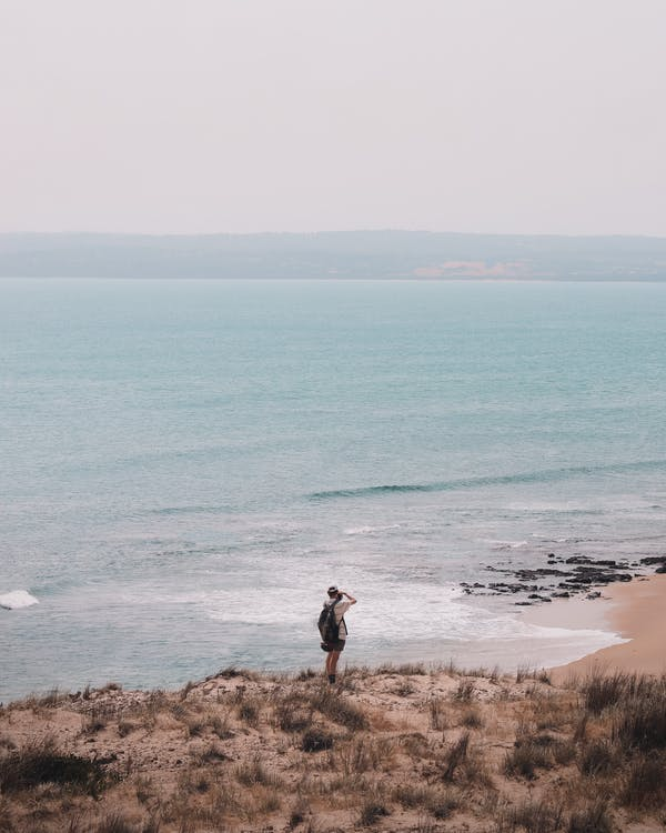 High angle back view of anonymous male backpacker shooting picturesque scenery of wavy sea while standing on sandy shore